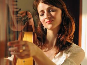 Woman plays celtic harp in folk style