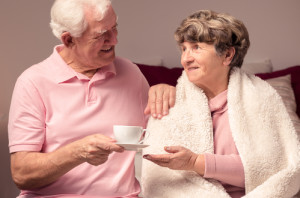 Supportive elderly man giving the cup of tea to his sick wife tucked with blanket